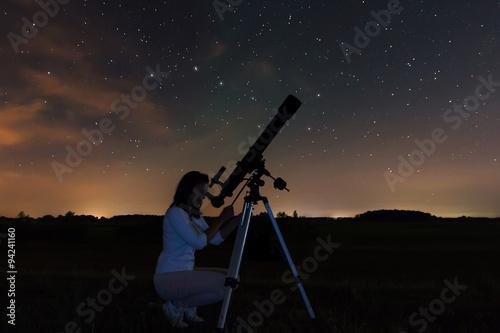 Woman looking through a telescope watching the stars Fotobehang