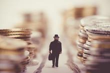 たくさんのお金が積まれている道を歩くビジネスマン