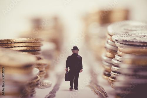 Photo たくさんのお金が積まれている道を歩くビジネスマン