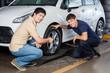 Smiling Customer With Mechanic Repairing Car