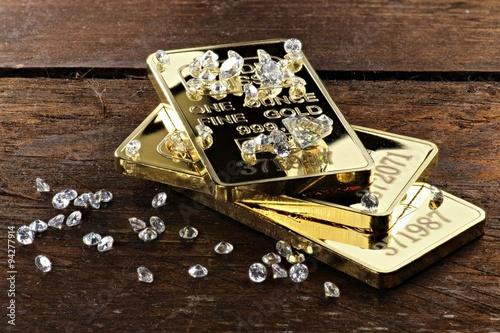 obraz dibond Goldbarren und geschliffene Diamanten auf rustikalem Holzhintergrund