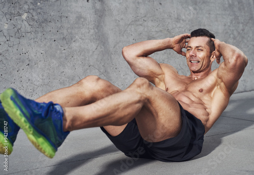 Fotografie, Obraz  Muscular male fitness athlete doing sit ups while smiling