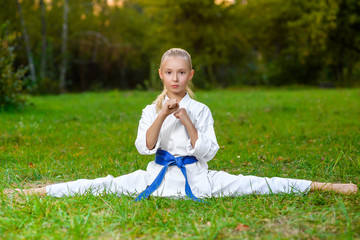 Fototapetagirl in white kimono during training karate exercises at summer
