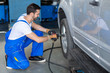 male mechanic repairing car wheel