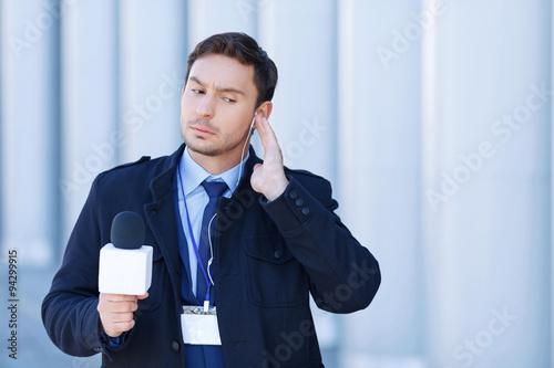 Valokuva  Journalist checks his gadgets before broadcast.