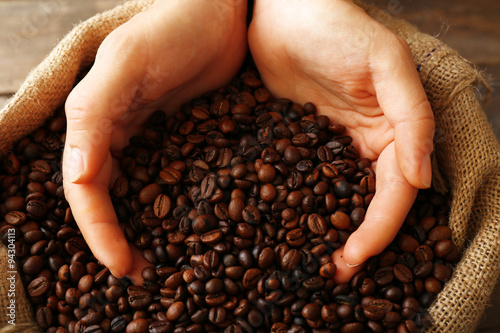 Tuinposter koffiebar Hands in sac with roasted coffee beans on wooden table