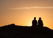 Silhouette Of Couple Sitting O...