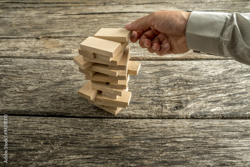 Fotografía  Male hand creating or building a tower of many wooden blocks