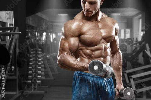obraz dibond Muscular man working out in gym doing exercises with dumbbells at biceps, strong male naked torso abs