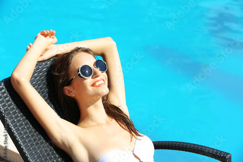 Photographie Young woman enjoying on sunbed at swimming pool