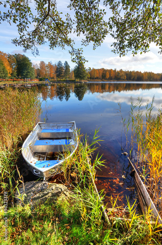 Vertical autumn landscape with aluminium boat