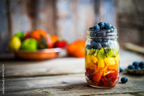 Fényképezés  Colorful fruit salad in a jar on rustic wooden background