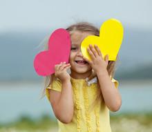 Happy Little Kid A Big Heart Are Walking In A Camomile Field