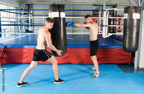 Strong boxer and opponent during a box fight in ring - 94353559