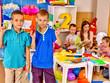 Children boy and girl with teacher in kindergarten .