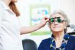 female doctor examines senior woman eye sight with phoropter