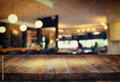 Fotografía  image of wooden table in front of abstract blurred background of restaurant ligh