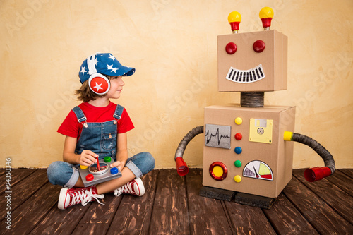 Foto  Happy child playing with toy robot