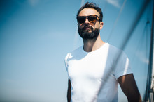 Bearded Man Wearing Sunglasses, Standing On A Yacht And Looking At The Horizon