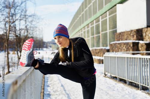 Photo sur Aluminium Glisse hiver Female runner stretching before running at winter