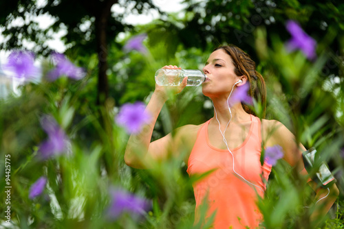 Fotografía  Woman drinking water from bottle during running or workout rest at city park on spring
