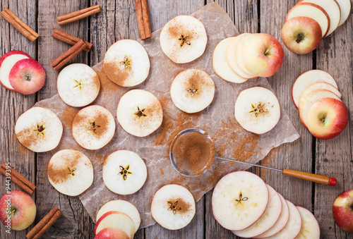 Fotografie, Obraz  Apples sliced with cinnamon on old wooden background