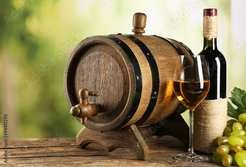 Papiers peints Affiche vintage White and red grape with wine bottle near barrel on wooden table, close up