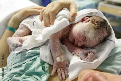 Fotografie, Obraz  Mother hugging a vernix covered newborn