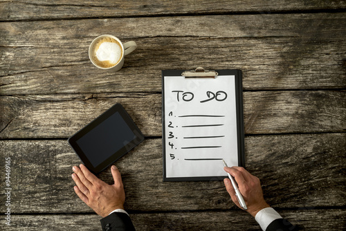 Photo  Top view of male hand writing a To do list on a white sheet of p
