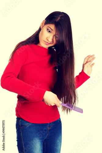 Fotografie, Obraz  Woman combing her tangled hair.