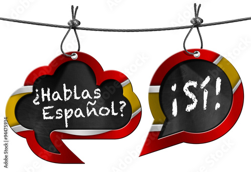 Hablas Espanol - Two Speech Bubbles / Two speech bubbles with Spanish flag and text Hablas Espanol? Si! Hanging from a steel cable and isolated on white
