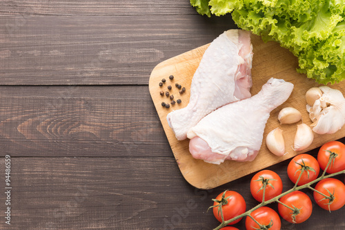 Photo  Ingredients and raw chicken leg on cutting board on wooden backg