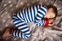 Cute Little Boy Sleeps In Pajames On Bed. Fokus Above