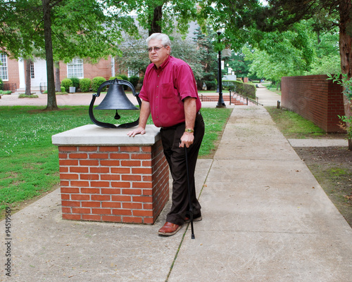 Fotografie, Obraz  Elderly Man With Cane Standing Beside a Bell in the Park
