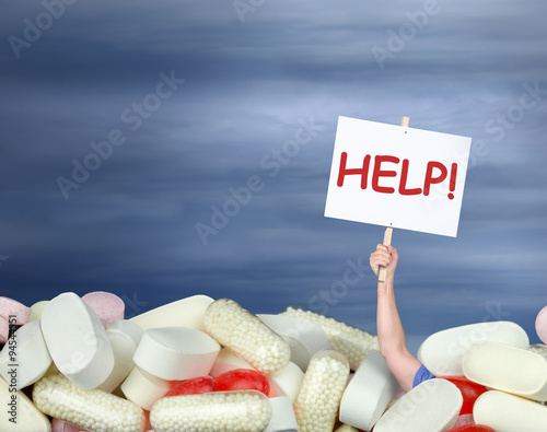 Fotografia  A huge pile of various pills with a man's hand coming out of the pills holding a sign that says HELP! representing drug abuse, addiction, chronic pain, medication confusion, and medical guidance help
