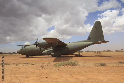 Fotografija Military aircraft lands on field airstrip to deploy troops