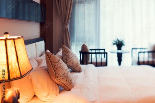 Fototapeta Night scene in hotel room: prepared fresh bed obraz