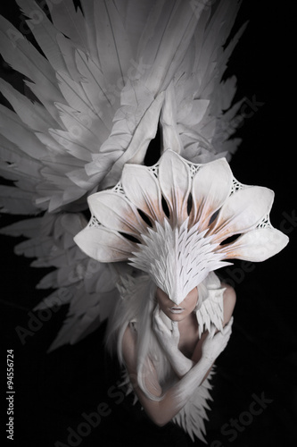 Fototapety, obrazy: Angel, costume, concept, cinematic, a portrait of a young girl and a white wig , which carries a large white mask and a large white wings. feathers costume and hands painted in white, look from up.