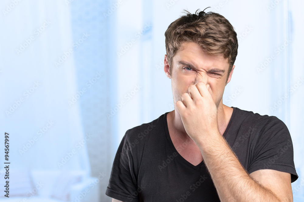 Fototapety, obrazy: Young Man holding his nose against a bad smell