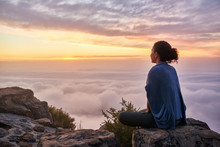 Woman On A Mountain Top Looking At Morning Clouds