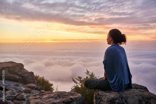 Fotomural Woman on a mountain top looking at morning clouds