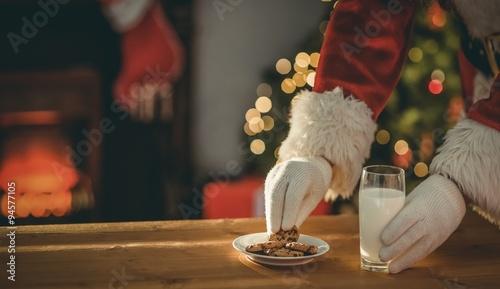 Fotografie, Obraz  Santa claus picking cookie and glass of milk