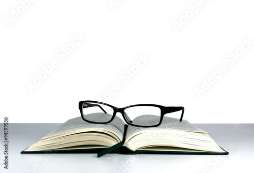 Fotografía  Book and reading glasses on a white table and white background