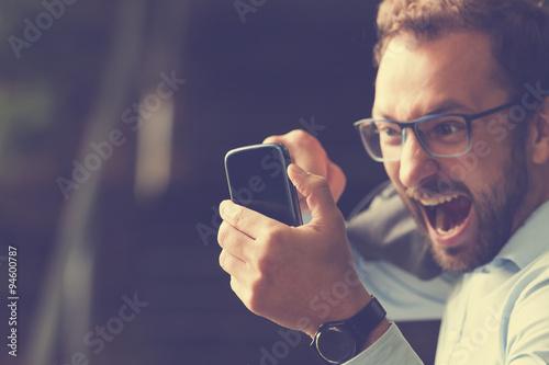 Cuadros en Lienzo  Angry gay biting the phone.