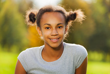 Portrait Of Beautiful African Girl Sitting In Park