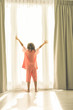Girl standing at window holding curtains open to look out of lar