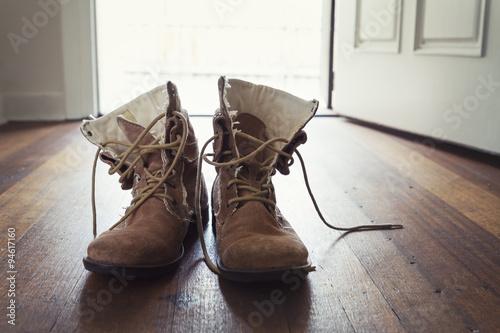 Fényképezés  Pair of men's worn leather boots in doorway of home