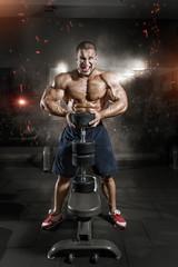 Fototapeta na wymiar Athlete muscular bodybuilder man demonstrates his muscles in gym