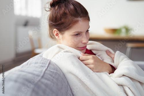 Foto  entspannte frau kuschelt sich in eine decke
