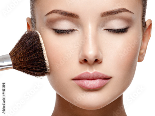 Poster  woman  applying dry cosmetic tonal foundation  on the face